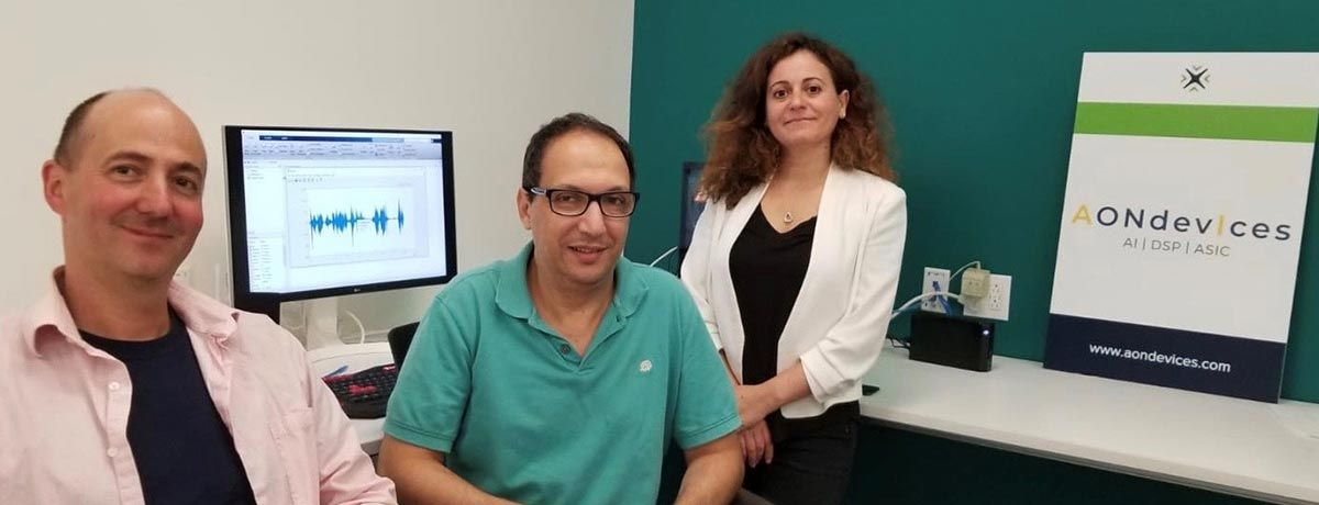Daniel Schoch (left), Dr. Adil Benyassine, and Mouna El Khatib (right) in the AONDevices office. Computer in background.